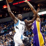 Minnesota Timberwolves' Gorgui Dieng, left, shoots as Los Angeles Lakers' Tarik Black defends during the first quarter of an NBA basketball game, Wednesday, March 25, 2015, in Minneapolis. (AP Photo/Jim Mone)