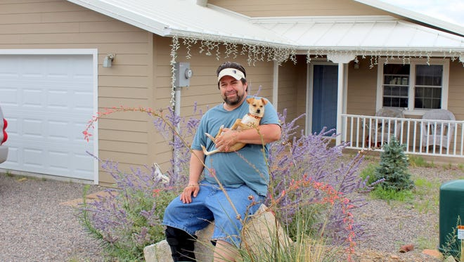 """Chris Arellano, 45, is a native Silver City resident who realized his dream of owning a home, thanks to a USDA rural housing program and land available at Vistas de Plata, an affordable home subdivision on Silver City's east side. He lives there with his son, Christopher, and three Chihuahuas. Pictured with Chris is """"Hero."""""""