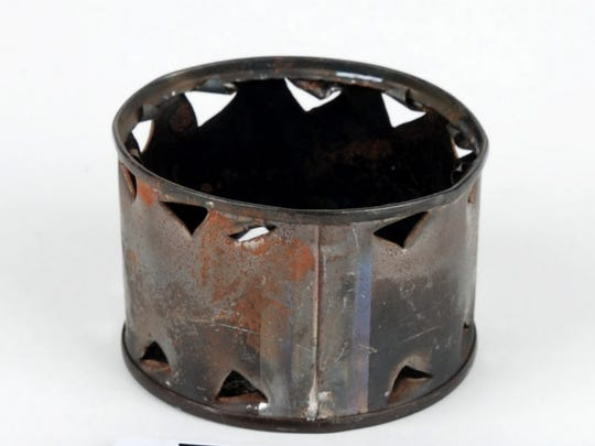 """Soldiers often repurposed C ration cans into tiny stoves like this item donated to the Wisconsin Veterans Museum by Navy chaplain Ray Stubbe of Milwaukee who used it during the 1968 battle of Khe Sanh in Vietnam. Military members in the field often had no way of heating their food because they were not allowed to make fires to prevent the enemy from detecting their location. In Vietnam some service members poked holes in ration tins and dropped in a small ball of plastic explosive or a purple """"heat tab"""" to rapidly heat their meal. Courtesy Wisconsin Veterans Museum"""