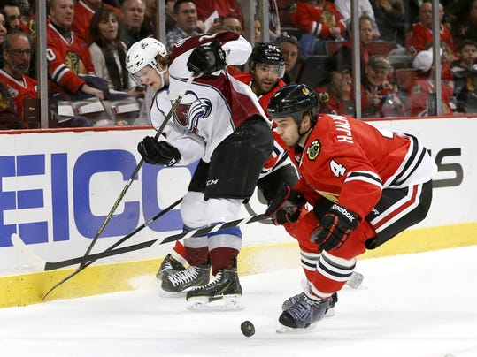 Colorado Avalanche center Nathan MacKinnon, left, loses the puck as Chicago Blackhawks defenseman Johnny Oduya, center, and defenseman Niklas Hjalmarsson (4) defend during the first period of an NHL hockey game Tuesday, March 4, 2014, in Chicago. (AP Photo/Charles Rex Arbogast)