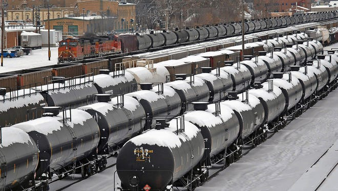 FILE - In this Dec. 31, 2013  file photo, oil cars are backed up in a yard in the aftermath of a train derailment in Mandan, N.D. U.S. senators from five states want the government to charge companies a fee to ship oil and other flammable liquids in older railroad tank cars that have been in numerous massive explosions. (Tom Stromme/The Bismarck Tribune via AP, File)