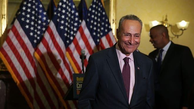 U.S. Sen. Charles Schumer (D-NY) (L) and Secretary of Transportation Anthony Foxx (R) leave after a news conference on the Transportation Bill July 9, 2015 on Capitol Hill in Washington, DC. Senate Democrats urged the Republicans to unveil their plan details for the bill.