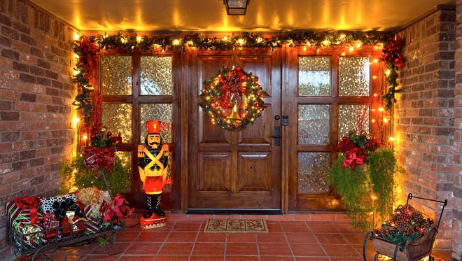 PHOTO BY EDDIE SEAL/SPECIAL TO THE CALLER TIMESThe front porch, illuminated the the colors of the season;  greets visitors to the home