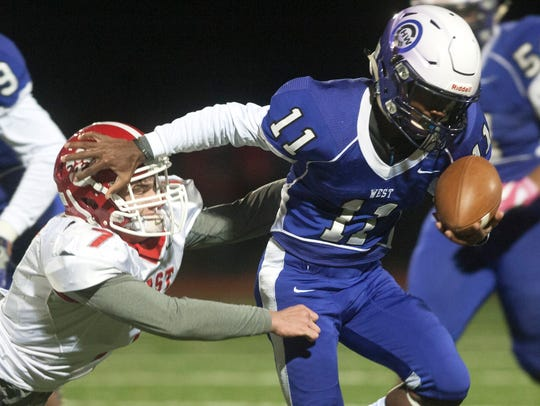Cherry Hill West's Monte Williams breaks the tackle