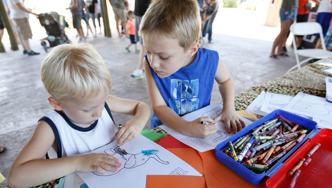 Rylan Swenson, 6, of Ankeny (right) checks on the work of his brother, Thayer Swenson, 4, as they color in a picture of an elephant Saturday, Aug. 6, 2016, as part of World Elephant and Rhino Day at the Blank Park Zoo in Des Moines. The event was held to raise awareness of elephant poaching and to help the conservation group 96 Elephants, which says about 96 elephants are killed each day for their ivory.