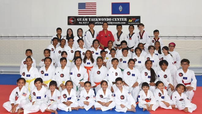 Guam Taekwondo Center chief instructor Noly Caluag, back row center poses with the students of the 6 pm class.