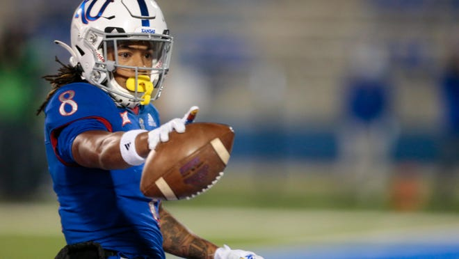 FILE -- Kansas wide receiver Kwamie Lassiter II points to the cameras after scoring a touchdown in the first quarter of a game at David Booth Kansas Memorial Stadium against TCU. TCU won the 2020 contest 59-23.