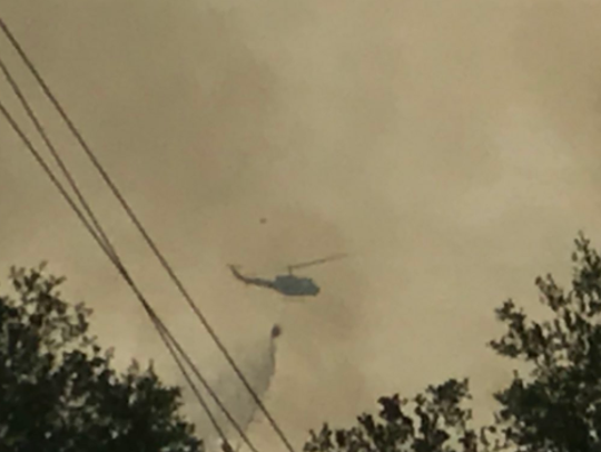 A helicopter drops water on the fire.