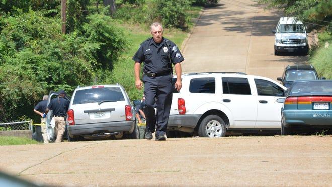 Police work at the Cummins Street shooting scene Monday.