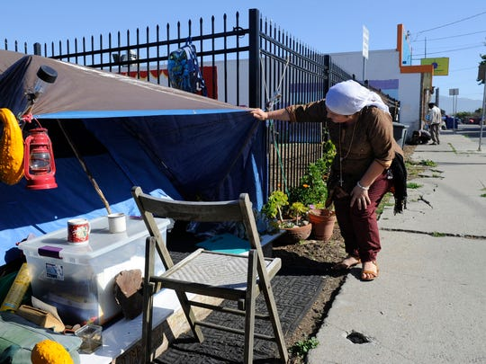 Rosa M. Barocio, 44, visits with a homeless man who wouldn't come out of his tent near Dorothy's Place where Barocio volunteers. She cooks the noon meal on the first Sunday of each month at the nonprofit.