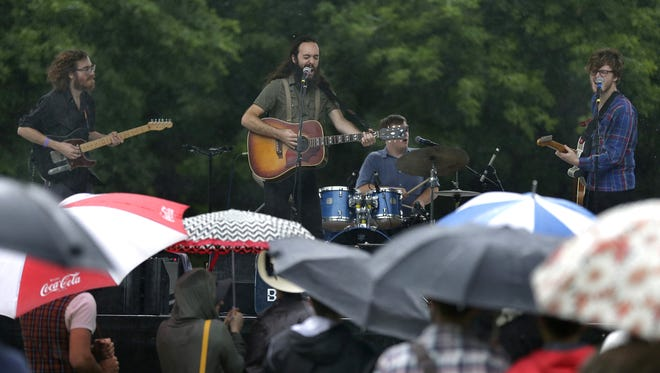 Fans under umbrellas gather as Cereus Bright performs at Jones Park Friday during the second day of the Mile of Music festival in Appleton.