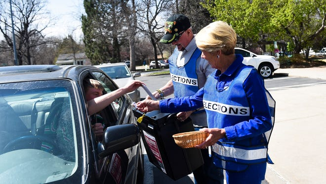 Cathy Morgan, right, and Pete Gomez help run a drive-by ballot box at city hall Tuesday, April 7, 2015, in Fort Collins, CO. Polls close tonight at 7 p.m.