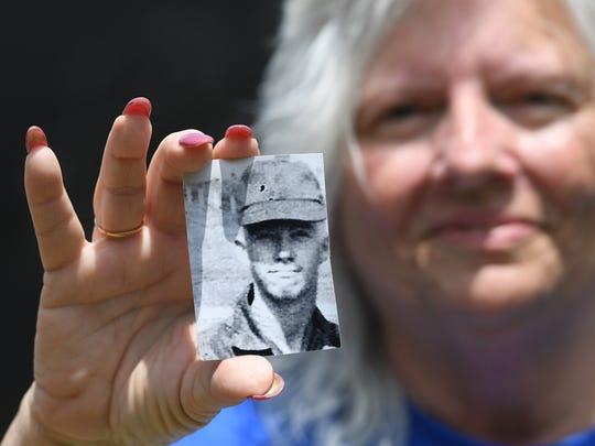 """Mary Louise Worthy holds a photo of her late husband Floyde Edward """"Eddy"""" Worthy Thursday, May 24, 2018. The photo was taken during his military service in Vietnam."""