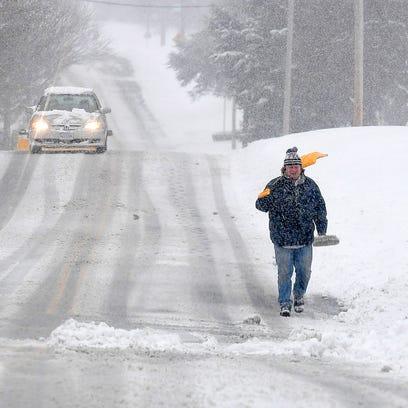 A man walks along Barterbrook Road with snow shovel