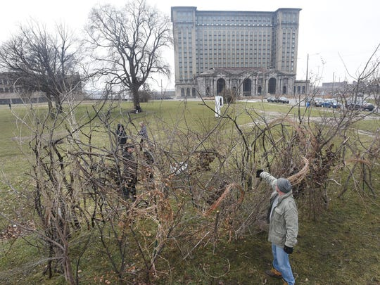 Volunteer Andy Arthur works Thursday with artist Lisa Waud and others to create an anti-Trump protest art piece in Roosevelt Park in the shadow of the vacant train station in Detroit.
