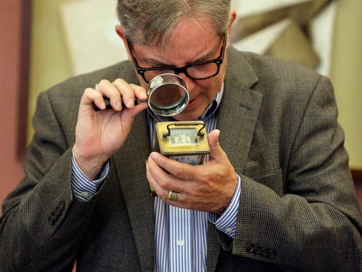 "Antiques Appraiser Mark Moran examines an old clock at Grace Episcopal Church during ""What's It Worth?"" Thursday July 24, 2014 in Sheboygan."