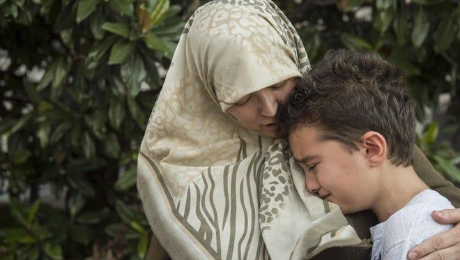 Lana Lockhart, who converted to Islam 26 years ago, consoles her son, Yaseen Ezzeir, during an interfaith prayer vigil on Sunday at Legislative Plaza on Sunday in downtown Nashville.