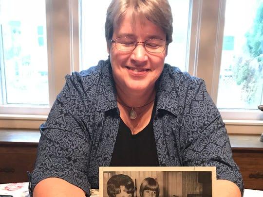 Amy Geishert, 54, shows a 1969 newspaper photo taken