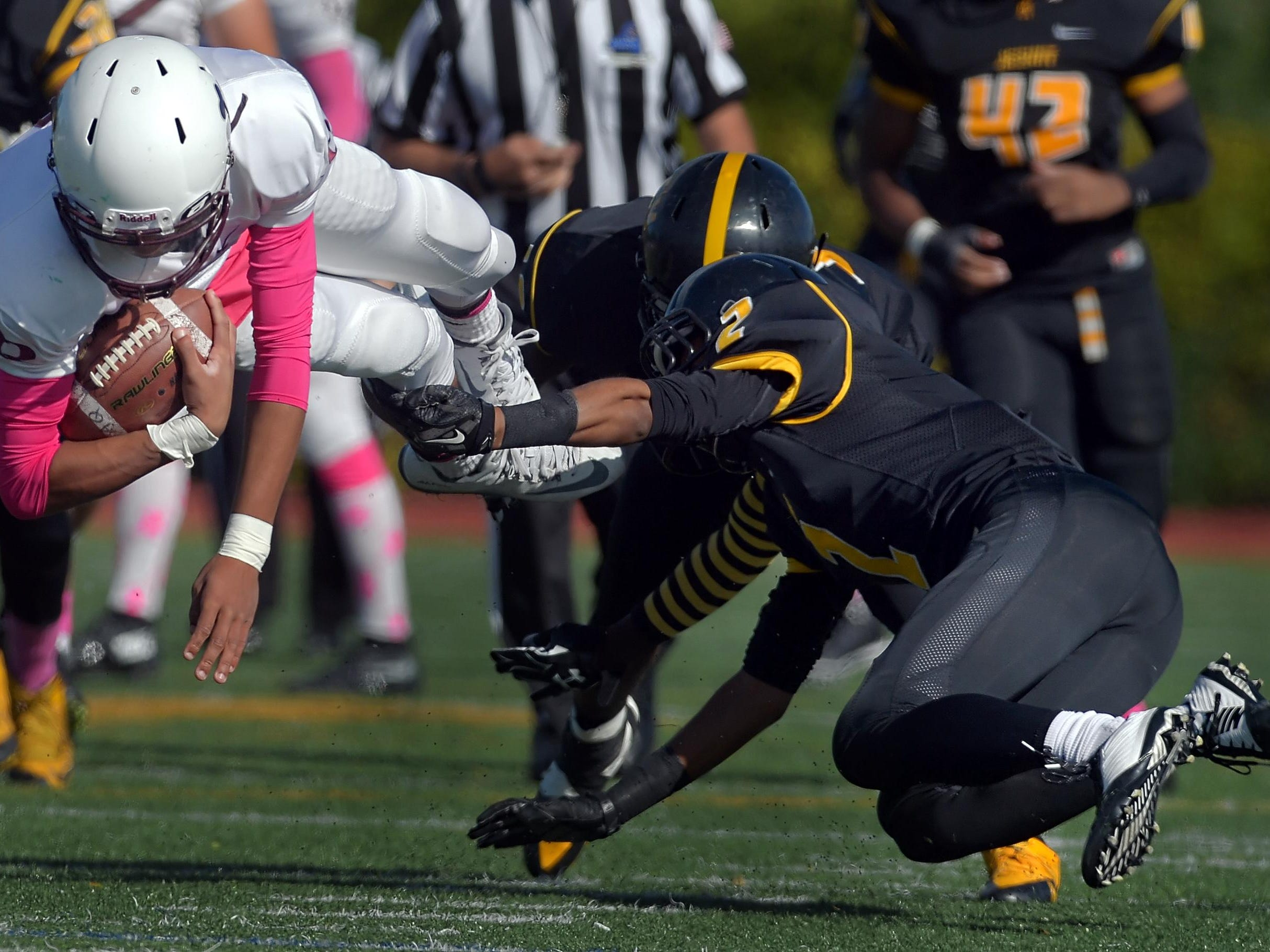 Aquinas' Jason Hawkes, left, is tripped up by McQuaid's Noah Williams during a regular season game played at McQuaid Jesuit High School on Saturday, October 10, 2015.