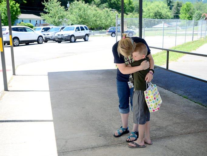 Kindergarten teacher Sarah Lowder hugs kindergarten