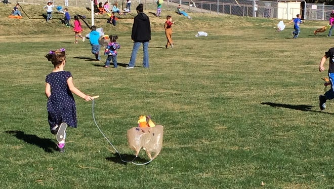 Nob Hill kindergardeners frolic on the green at the Horton Stadium Friday with the plastic bag kites they made in class to celebrate Spring.