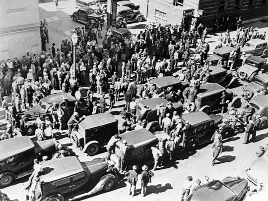 Cars and UAW members block the street outside the old