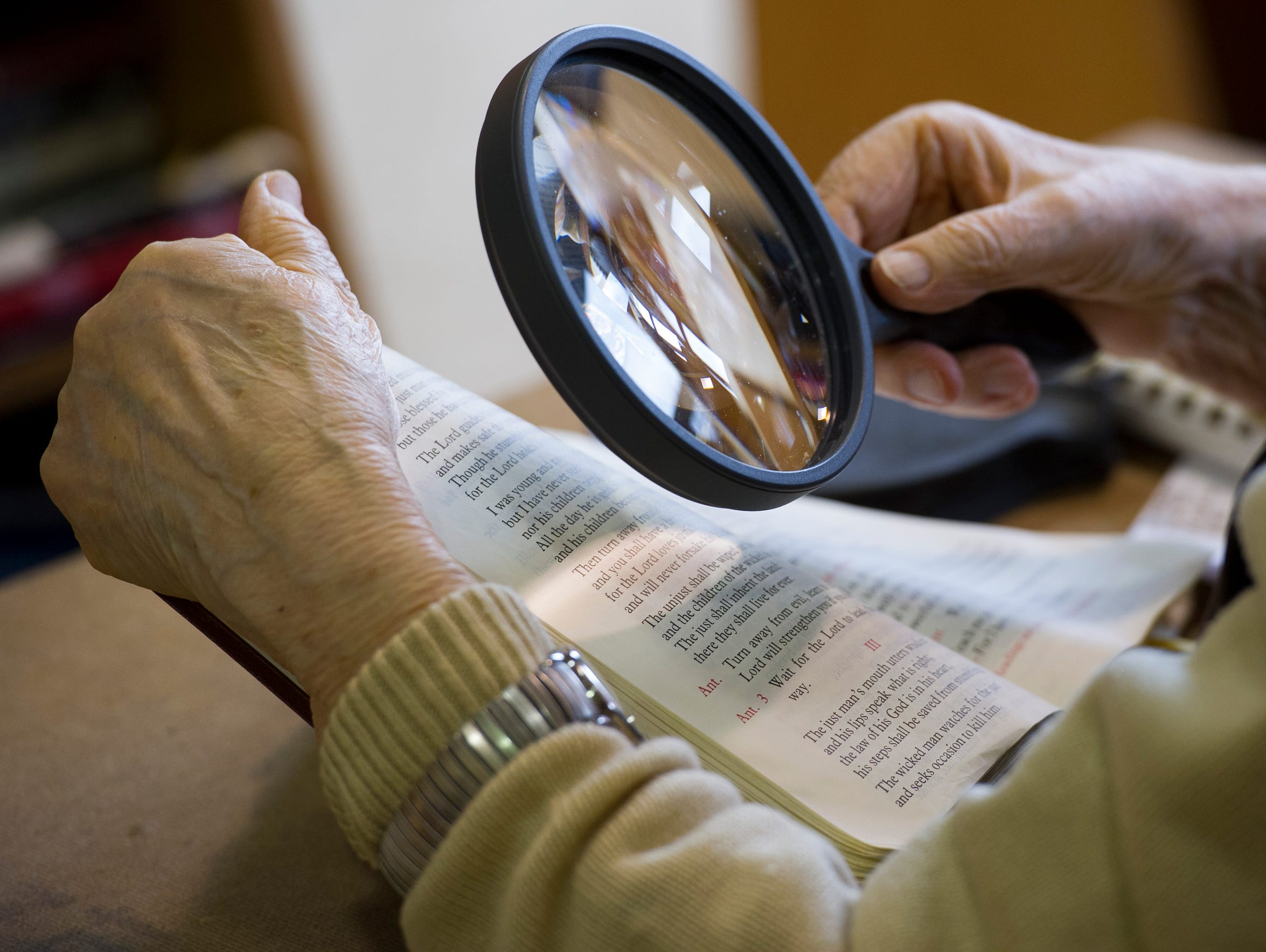 Sister Marie Carmel Fisk, uses a magnifying glass to