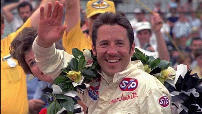 """ADVANCE FOR WEEKEND EDITIONS, OCT. 8-9 -- FILE -- Mario Andretti celebrates victory in the 1969 Indianapolis 500. Andretti will complete his season-long """"Arrivederci, Mario"""" Tour on Sunday in the Bank of America 300 at Laguna Seca Raceway, where he will race in his 407th and last Indy-car event.(AP Photo/File)"""