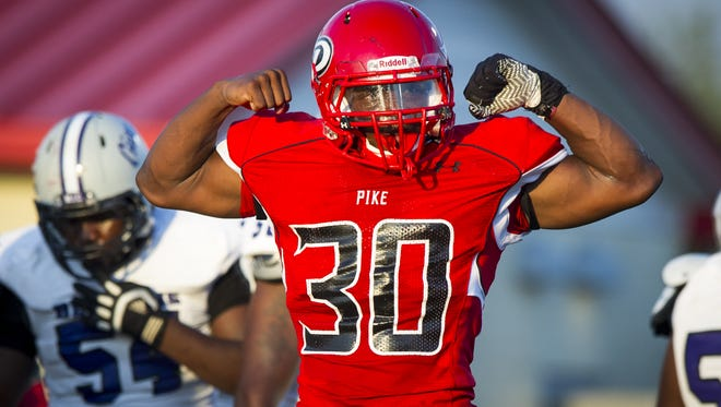 Pike High School junior Aaron Jones (30) reacts to stopping Ben Davis High School senior Dorian Tate (24) in the backfield during the first half of action. Pike High School hosted Ben Davis High School in varsity football action, Friday, September 5, 2014.