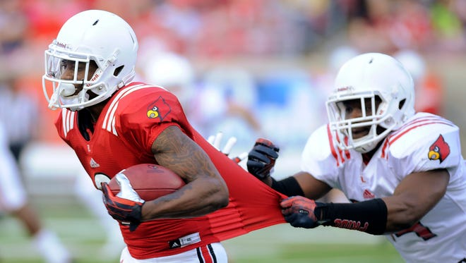 Louisville's Lyn Clark (right) tries to reel in DeVante Parker (left) on Friday during the 2014 UofL Football Spring game at Papa John's Cardinal Stadium. April 11, 2014