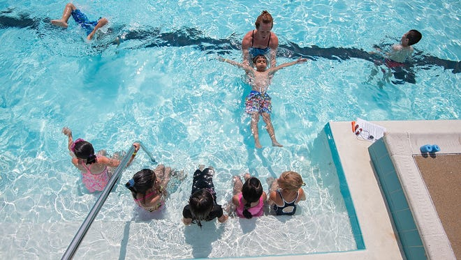 A pool supervisor helps a student with a back float during a swimming lesson on June 20, 2014, in Harrisonburg, Va.