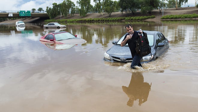Jim Sampson retrieves items from his 2002 Toyota Corolla stuck in flood waters on Interstate 10 east after rains flooded the freeway in Phoenix on Sept. 8, 2014.