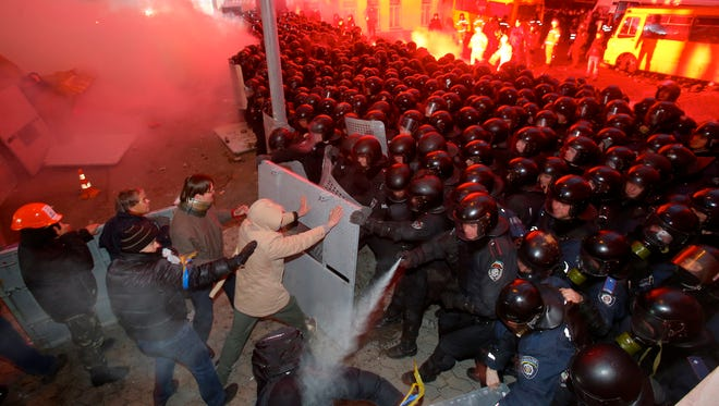 Protesters clash with police guarding the presidential administration building in downtown Kiev, Ukraine, on Sunday, Dec. 1, 2013.