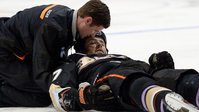 A trainer examines Anaheim Ducks winger Dustin Penner after he was hit by the Dallas Stars' Ryan Garbutt.