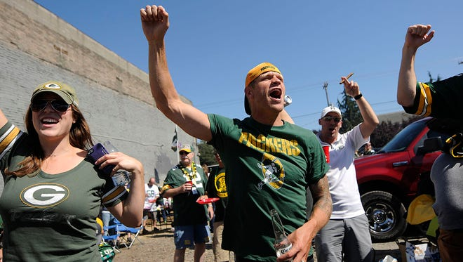 In middle, Jay DeMerit, originally from Green Bay and former MLS professional soccer player with Vancouver, Amy Trgovac, Laurel Petti and Blake Russum have some fun during a Northwest Packer Backers party before Thursday's game in Seattle