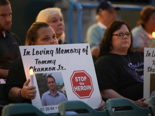 People hold signs as they participate in a candlelight vigil at the Camden's waterfront stadium in remembrance of those who have died from drug overdoses.