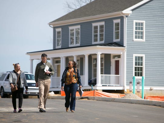 Whitehall project manager Steve Marshall shows Beverly Powers of Wilmington (right) and her real estate agent Donna Bond model homes in the Middletown development. The project seeks to create a walkable neighborhood of residences and businesses.