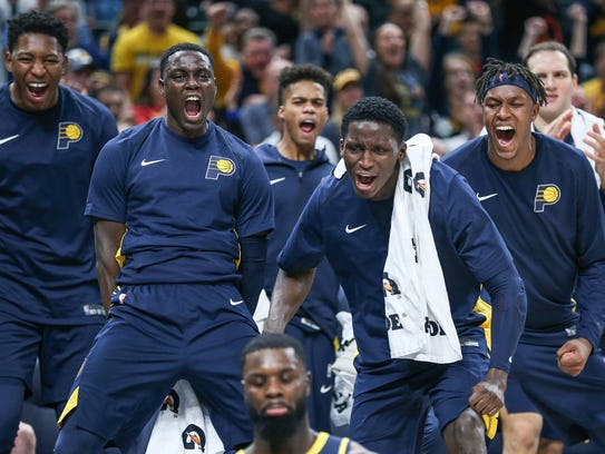 Players on the Indiana Pacers bench react to a call