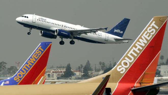 A JetBlue plane flies over a pair of Southwest Airlines jets on July 19, 2005, at Bob Hope Airport in Burbank, Calif.