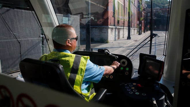 Jamie Woodall, operator for the Cincinnati Bell Connector, guides the streetcar through Over-the-Rhine during a media preview Tuesday Sept. 6, 2016.