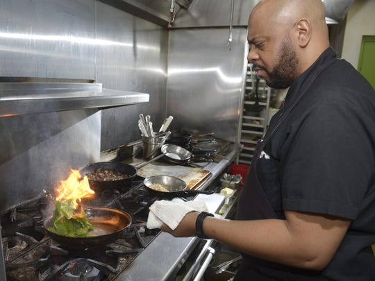 Chef Christopher Thompson, of Osteria 222, prepares spinach to accompany an order at the Dearborn restaurant.