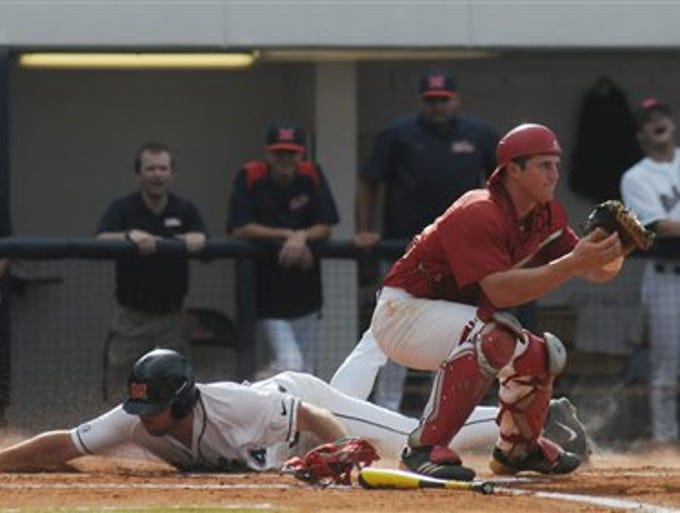 Ole Miss' Sikes Orvis, left, scores behind Jacksonville State's Stephen Bartlett, right, at the NCAA Oxford Regional at Oxford-University Stadium on Saturday, May 31, 2014.  (AP Photo/Oxford Eagle, Bruce Newman)