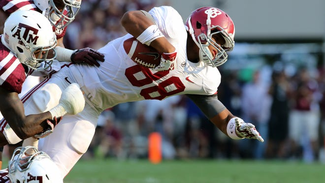 Alabama tight end O.J. Howard (88) leans for extra yards as he is tackled by Texas A&M defensive backs Clay Honeycutt (25) and Deshazor Everett (29) during the second half last Saturday at Kyle Field. . Alabama beat the Aggies 49-42.