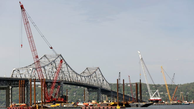 Construction crews use barges and cranes as work continues on a replacement for the 58-year-old Tappan Zee Bridge spanning the Hudson River, Tuesday, May 13, 2014, near Tarrytown, N.Y.