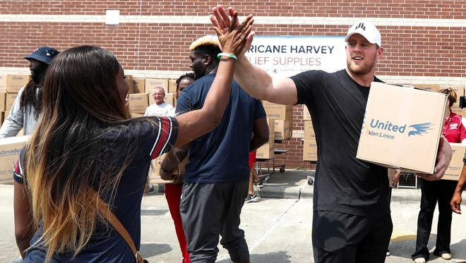 Anna Ucheomumu, left, high fives Houston Texans defensive end J.J. Watt after loading a car with relief supplies to people impacted by Hurricane Harvey on Sunday, Sept. 3, 2017, in Houston. J.J. Watt's Hurricane Harvey Relief Fund.