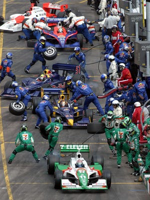 Tony Kanaan (bottom) drives away from the crowded pit area during lap 77 of the XM Satelite Indy 200 on March 19, 2005, at Phoenix International Raceway in Avondale, Ariz. Sam Hornish Jr. won the race with teammate Helio Castroneves finishing second.