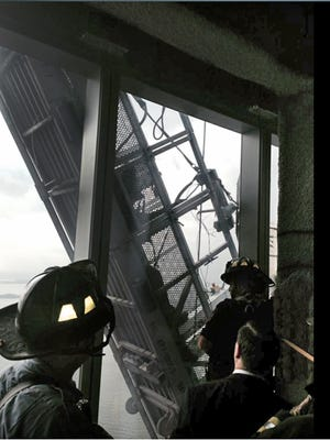 "This photo provided by the New York City Fire Department shows a window washer's gondola as it hangs from 1 World Trade Center, in New York, Wednesday, Nov. 12, 2014. Police official, John Miller, said the partially collapsed scaffolding hung at ""a 75-degree angle.""  (AP Photo/New York City Fire Department)"