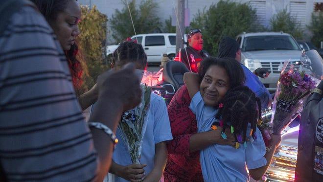 Arneatha Reynolds, wife of Highland Park Officer Robert Ball, hugs neighbor Amy, 7, during a vigil on Monday to honor the slain officer.
