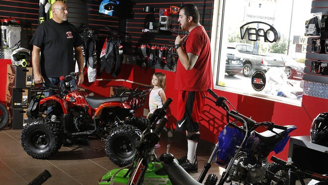Mark Goolie, left, sales manager at Independent Motorsports in Columbus, talks with Chuck Gilliam of Orient on Wednesdsay about the safety features on the Coolster 125CC All-Terrain Vehicle, including a remote kill switch and throttle limiter. Gilliam is looking for an ATV for his three children, including 3-year-old daughter Aria Kemper, who is with him.