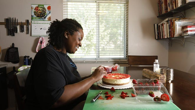 "Sadaya ""Daisy"" Lewis prepares cheesecake for a customer at her Columbus home June 12. Lewis was six weeks away from opening a restaurant when the coronavirus pandemic shut down the economy. She has been baking on the side to help pay bills."